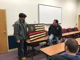 Officer Ashe's Husband Kevin presenting Chief 38 with the Flag