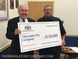 Company President John Carbo accepts check from Senator Rafferty